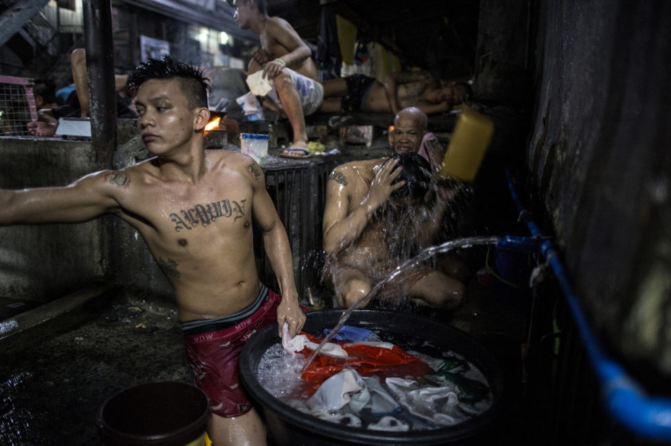 In this photo taken on July 21, 2016 an inmate (C-top) cooks his dinner as other detainees take a bath inside the Quezon City jail at night in Manila. There are 3,800 inmates at the jail, which was built six decades ago to house 800, and they engage in a relentless contest for space. Men take turns to sleep on the cracked cement floor of an open-air basketball court, the steps of staircases, underneath beds and hammocks made out of old blankets. / AFP PHOTO / NOEL CELIS / TO GO WITH AFP STORY: Philippines-politics-crime-jails, FOCUS by Ayee Macaraig