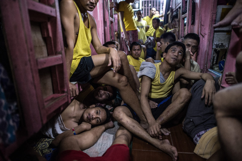 Inmates rest in their sleeping quarters inside the Quezon City jail at night in Manila in this picture taken on July 18, 2016. There are 3,800 inmates at the jail, which was built six decades ago to house 800, and they engage in a relentless contest for space. Men take turns to sleep on the cracked cement floor of an open-air basketball court, the steps of staircases, underneath beds and hammocks made out of old blankets. / AFP PHOTO / NOEL CELIS / TO GO WITH AFP STORY: Philippines-politics-crime-jails, FOCUS by Ayee Macaraig