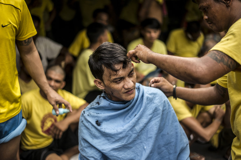 An inmate gets a haircut inside the Quezon City Jail in Manila in this picture taken on July 18, 2016. There are 3,800 inmates at the jail, which was built six decades ago to house 800, and they engage in a relentless contest for space. Men take turns to sleep on the cracked cement floor of an open-air basketball court, the steps of staircases, underneath beds and hammocks made out of old blankets. / AFP PHOTO / NOEL CELIS / TO GO WITH AFP STORY: Philippines-politics-crime-jails, FOCUS by Ayee Macaraig