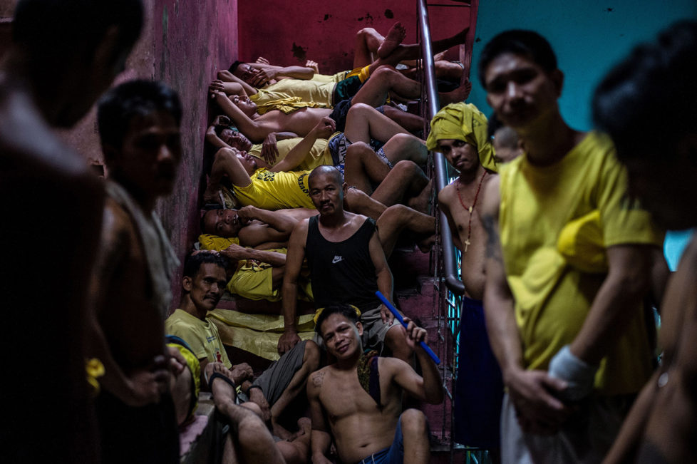 Inmates sleep on the steps of a ladder inside the Quezon City jail at night in Manila in this picture taken on July 18, 2016. There are 3,800 inmates at the jail, which was built six decades ago to house 800, and they engage in a relentless contest for space. Men take turns to sleep on the cracked cement floor of an open-air basketball court, the steps of staircases, underneath beds and hammocks made out of old blankets. / AFP / NOEL CELIS / TO GO WITH AFP STORY: Philippines-politics-crime-jails, FOCUS by Ayee Macaraig (Photo credit should read NOEL CELIS/AFP/Getty Images)