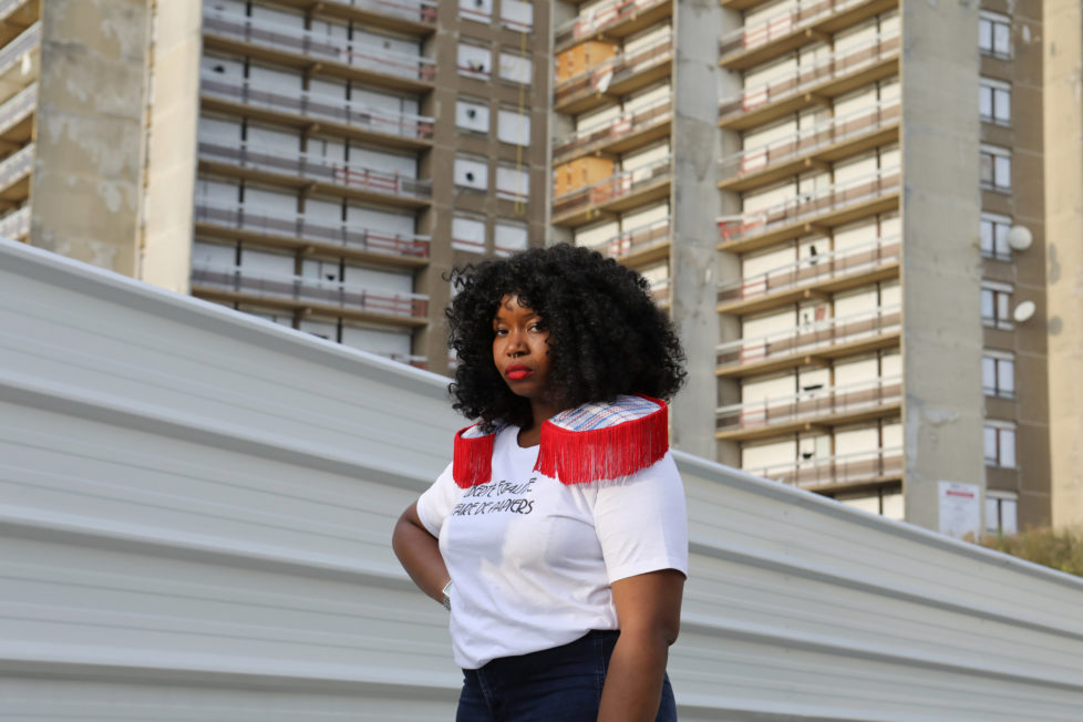 "Designer Aisse N'diaye poses for a picture wearing a shirt from her brand Afrikanista in Clichy-sous-Bois, France, August 26, 2016. N'diaye grew up in Clichy-sous-bois, where her parents currently reside. Behind her is the La Forestiere housing where she grew up, and which is now slated for demolition. REUTERS/Joe Penney SEARCH ""CREATIVE BANLIEUE"" FOR THIS STORY. SEARCH ""WIDER IMAGE"" FOR ALL STORIES. THE IMAGES SHOULD ONLY BE USED TOGETHER WITH THE STORY - NO STAND-ALONE USES."
