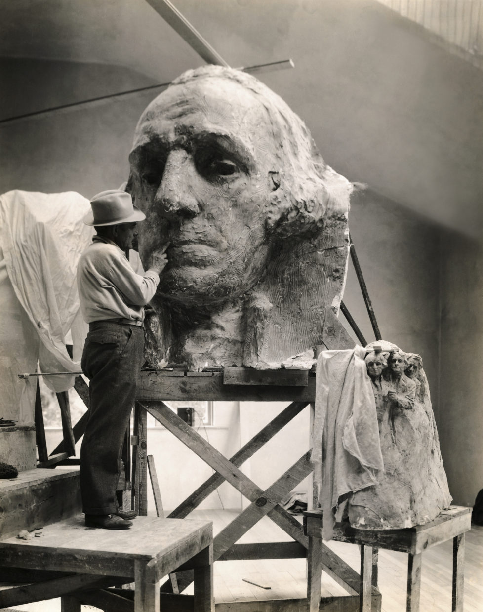 (Original Caption) Gutzon Borglum, America's famous sculptor, seen in his studio at Rushmore in the Black Hills of South Dakota, is working on the head of Washington. The small model of the heroic memorial is shown at right. The head of Washington is five stories high from chin to top. (Photo by George Rinhart/Corbis via Getty Images)