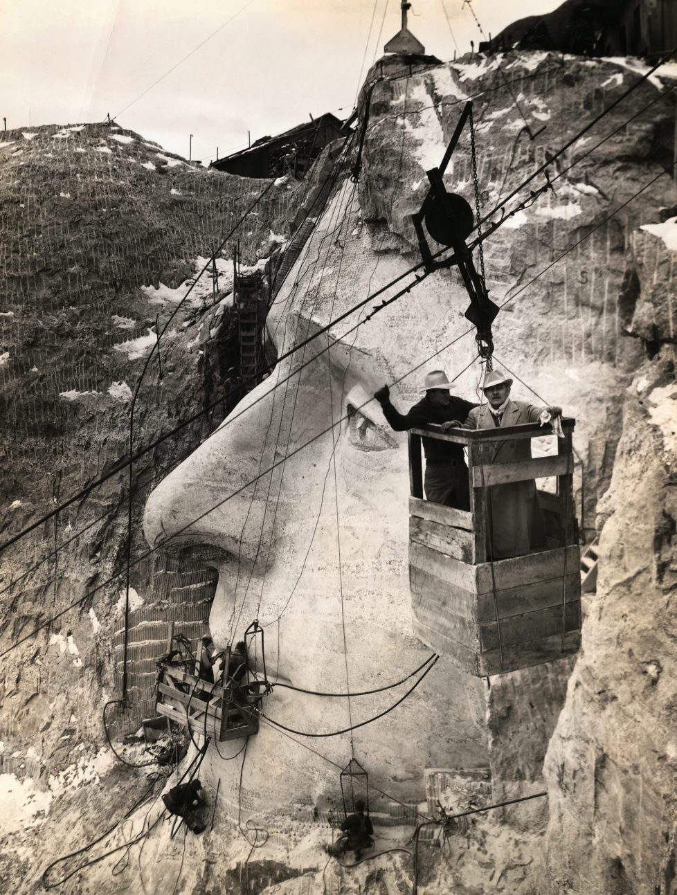American sculptor Gutzon Borglum, who is leading the Mount Rushmore National Memorial project, and his son, Lincoln, inspect the Jefferson head from an aerial tram. (Photo by George Rinhart/Corbis via Getty Images)