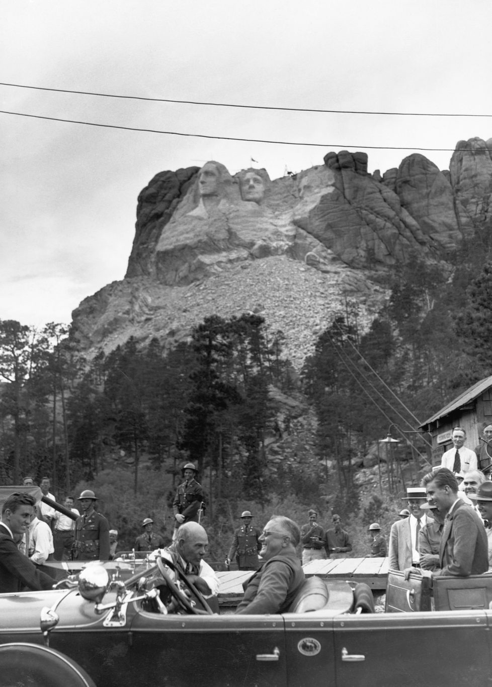 President Franklin Roosevelt talks with Mount Rushmore sculptor Gutzon Borglum during a trip to dedicate the sculpture of Thomas Jefferson. The President's sons, Franklin Jr. (far left) and John (far right) accompanied the President on this trip. | Location: Near Keystone, South Dakota, USA.
