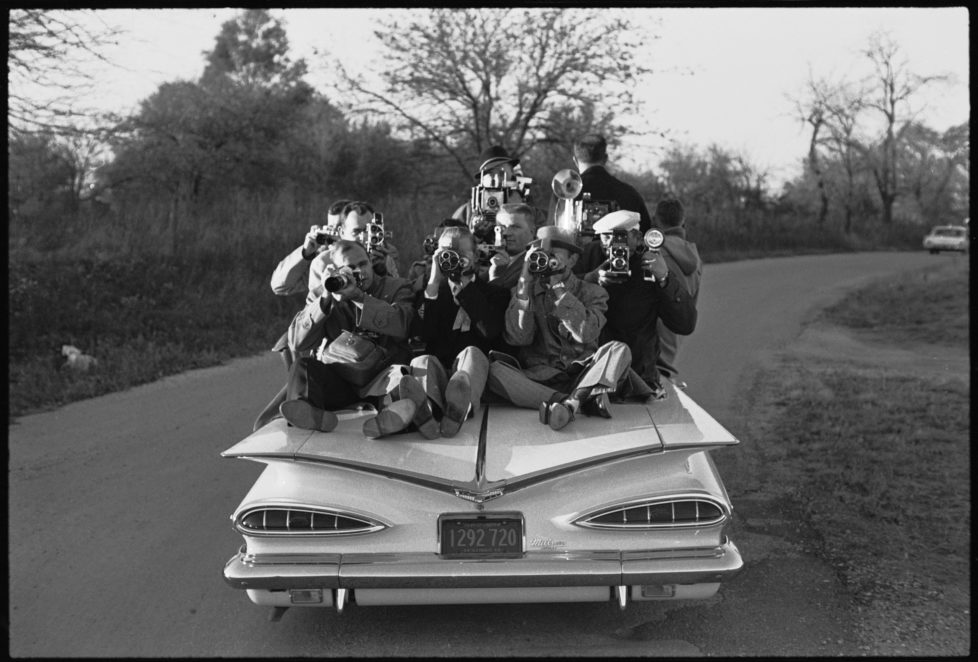 Members of the press perch on the trunk of a car as they cover the John F. Kennedy presidential campaign, Illinois, 1960. (Photo by Paul Schutzer/The LIFE Picture Collection/Getty Images)