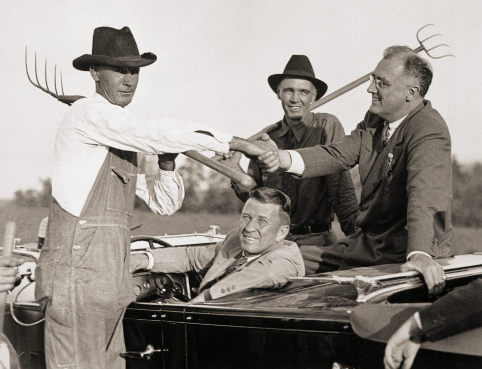 (Original Caption) 10/24/1932 -Atlanta, GA- Governor Franklin D. Roosevelt of New York has stressed helping the farmer in quite a few of his campaign speeches, and here he is getting first-hand information and shaking hands with men of the soil near Atlanta, GA. BPA2# 79