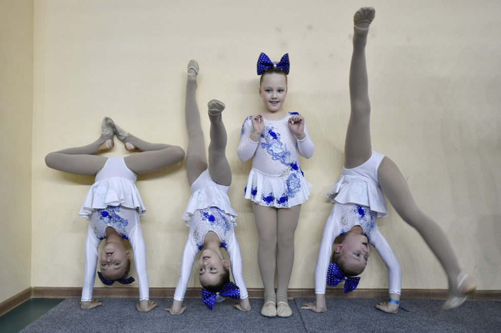 Members of a cheerleading team warm-up during the Russian Cheerleading Championship of students in Moscow on November 20, 2016. / AFP PHOTO / Natalia KOLESNIKOVA