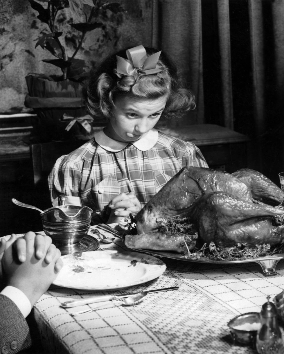 A young girl in a gingham dress with a white collar and a hair ribbon eyes the Thanksgiving turkey hungrily whilst prayers are being said around the table prior to Thanksgiving dinner in the USA, circa 1950. (Photo by Popperfoto/Getty Images)