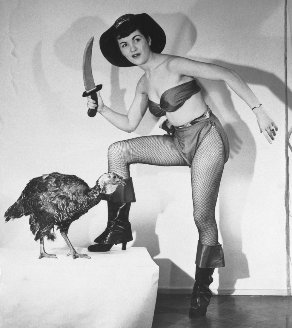 (Original Caption) The pretty buccaneer is Flo Bondi, who was Miss Ohio of 1949, but it makes little difference to the despondent turkey whether the ax is applied by a Venus or a Virago. The effect on its neck is the same. Flo is publicizing Thanksgiving and, incidentally, a motion picture called The Pirates of Capri.