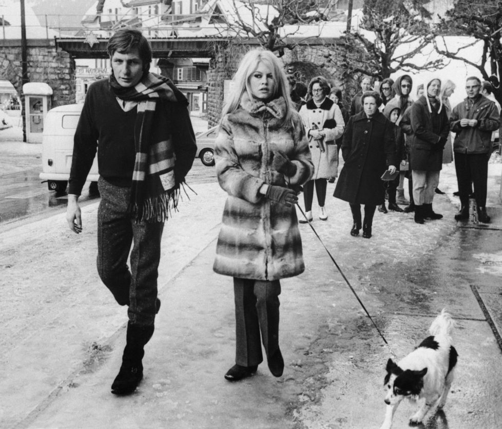 (Original Caption) Gstaad, Switzerland: French actress Brigitte Bardot and her husband, Gunther Sachs, walk their dog through the streets of Gstaad watched by curious onlookers. The couple is winter vacationing at the famous ski resort here. 1/5/1967