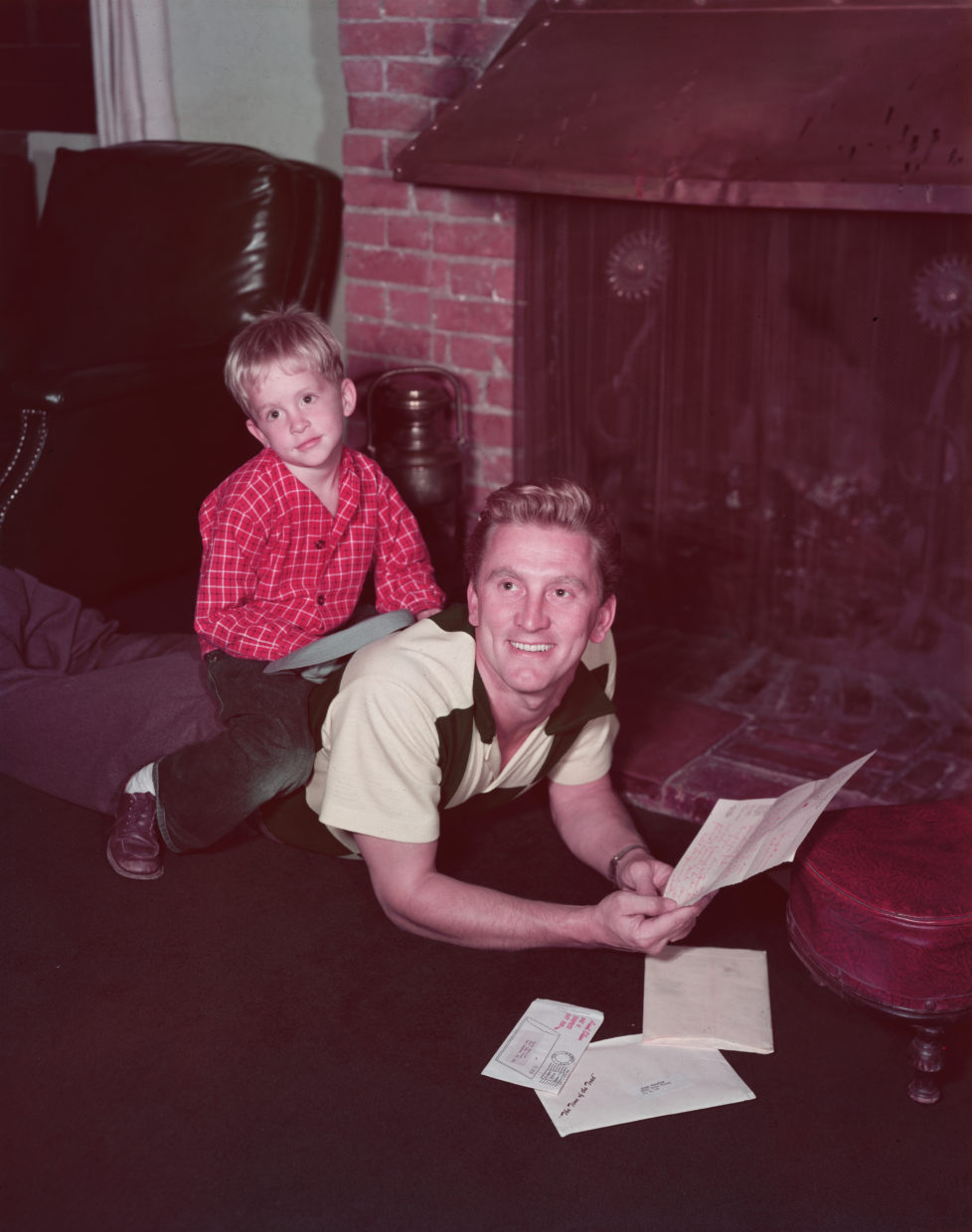 circa 1955: American actor Michael Douglas as a young boy, lounging with his father, the American actor Kirk Douglas, in front of a brick fireplace. Kirk is lying on his stomach and reading his mail as Michael sits on his back. (Photo by Hulton Archive/Getty Images)